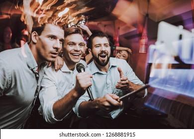 Young People. Dance Club. Sing. Microphone.Nightclub. Party Maker. Birthday. Karaoke Club. Celebration. Handsome Men. Beautiful Girls. Dancing People. Men Sing. Boys. Great Mood. Against the Backdrop.