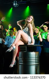 Young people dancing in club or disco and have party, the girls and boys, friends, having fun