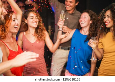 Young people dancing and driking champagne at weekend party night - Happy firends throwing confetti and having fun together - Entertainment, friendship and youth concept - Focus on left girl face