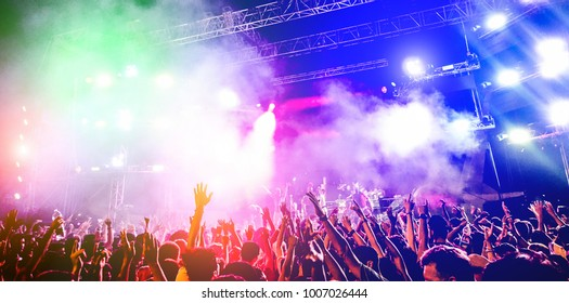 Young people dancing and having fun in summer festival party outdoor - Crowd with hands up celebrating concert event - Soft focus on center hand with yellow background flare - Fun and youth concept
