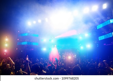 Young people dancing and having fun in summer festival party outdoor - Crowd with hands up and smarphones celebrating fest concert event - Soft focus on right hand with blue back flare