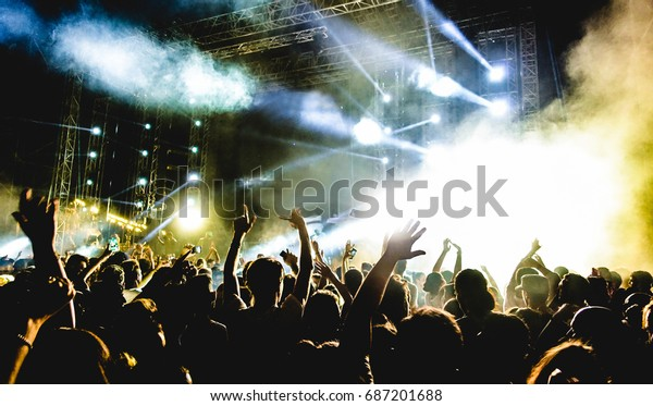 Young people dancing and having fun in summer festival party outdoor - Crowd with hands up celebrating fest concert event - Soft focus on center bottom hand with background flare - Contrast filter