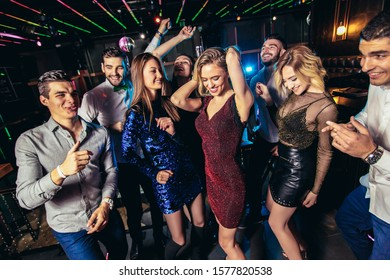 Young people dancing in night club and having fun