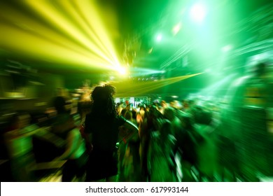 Young people dancing in night disco club with color laser lights in background - Concept of nightlife with music entertainment - Focus on black afro hair woman head - Radial defocused editing