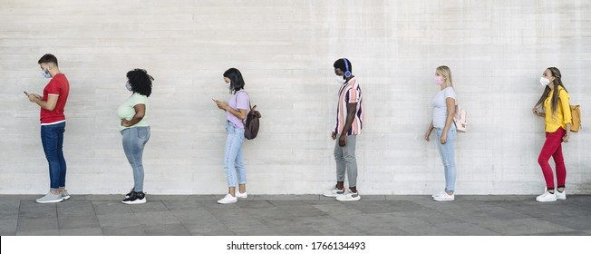 Young people from different cultures and race waiting in queue outside shop market while keeping social distance - Corona virus spread prevention concept - Shutterstock ID 1766134493