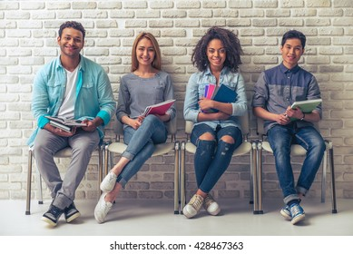 Young people of different nationalities are holding books and notebooks, looking at camera and smiling while waiting for interview