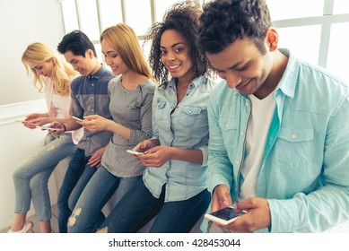 Young people of different nationalities using smartphones and smiling while sitting in a row