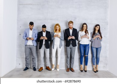 Young people with digital tablet standing by the grey wall