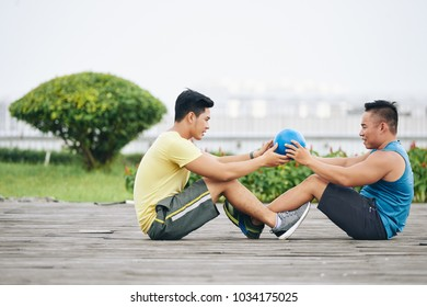 Young people doing abs exercise with ball