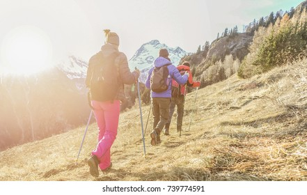 Young people doing trekking excursion in french high mountains - Hikers walking in alps with back sun light - Survival,travel and adventure concept - Focus on right girl - Warm filter