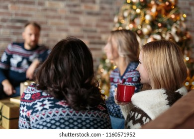 Young people dressed warm Christmas jerseys talking while chilling in a living room