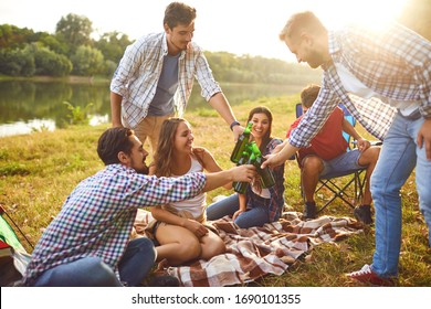 Young people drink, eat and clink glasses at a picnic