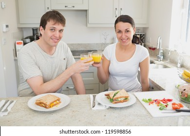 Young people drinking orange juice and eating sandwiches in the kitchen