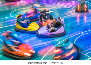 Young people driving bumper car at amusement park