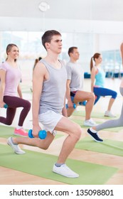 Young people with a dumbbell in fitness club