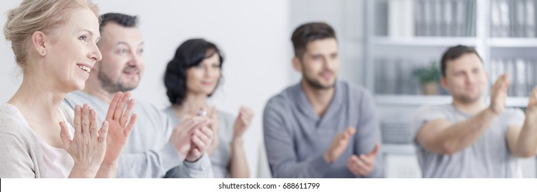 Young people during therapy at white office clapping their hands