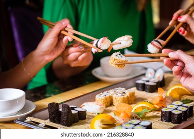 Young people eating sushi in Asian restaurant