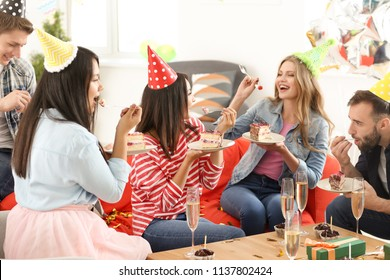 Young people eating tasty cake at birthday party indoors