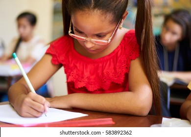 Young people and education. Group of hispanic students in class at school during lesson. Girl with paper for admission test, examination