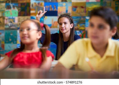 Young people and education. Group of students in class at school during lesson. Girl raising hand and asking question to professor