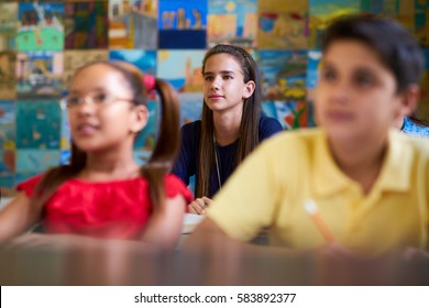Young people and education. Group of students in class at school during lesson. Focus on girl listening to teacher
