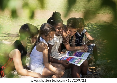 Young people and education, two little girls and boys reading book in city park