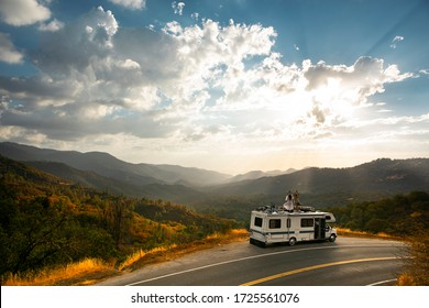 Young people enjoy freedom and an epic nature mountain view from the roof top of an RV motorhome. Travelling lifestyle roadtrip adventure in the USA