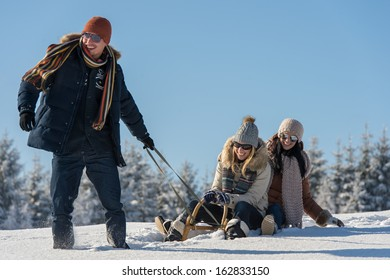Young people enjoy sunny winter day sledge man pulling girlfriends