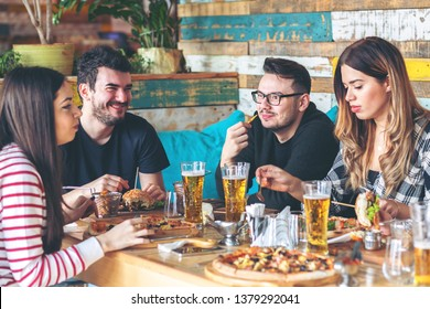 Young people enjoying time together eating burgers and pizza at restaurant – happy group of friends having fun dining in rustic pub serving beer, french fries and hamburgers
