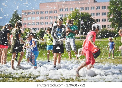 Young people in the foam. A foam party. Group of children having fun, enjoying and dancing at a foam party in aqua park. Outdoor view of foam machine. Rezekne - Latvia, 2020