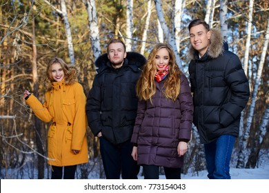 Young people in the forest. Fashion shot. Down Jackets.