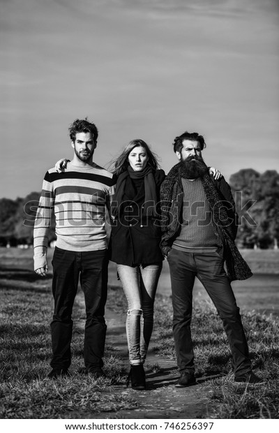 Young people friends of pretty cute sexy girl or woman and two bearded men outdoors in park on autumn sunny day on natural blue sky background
