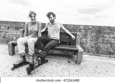 Young people friends in training suit with roller skates. Woman and man relaxing on bench outdoor.