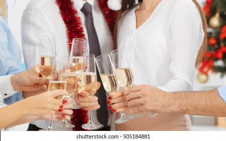 Young people with glasses of champagne celebrating Christmas at corporate party, close up view