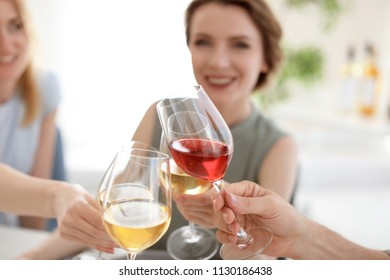Young people with glasses of delicious wine indoors