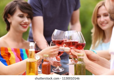 Young people with glasses wine at table outdoors. Summer barbecue
