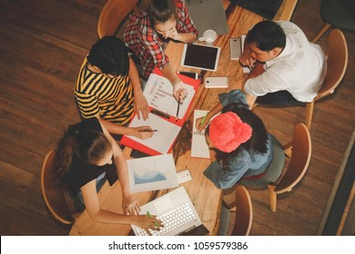 Young people in a group of 5 people working in the field of business management on a wooden table. Selective Focus