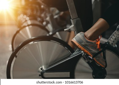 Young People - group of women and men - doing sport biking in the gym for fitness /Health care concept/ Tone warm lights