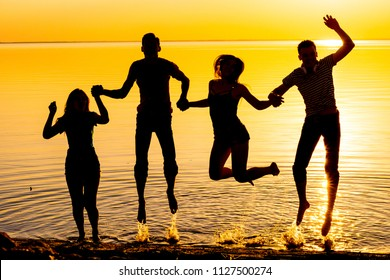 Young people, guys and girls, students are jumping against the sunset background, silhouettes