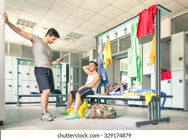 Young people at gym dressing room - Handsome guys at fitness studio doing their own staff before training - Social concept with lack of communication - Man looking at smartphone not talking to friends