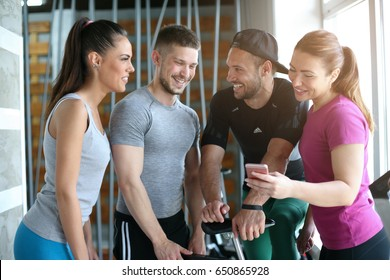 Young people in gym. Friends workout in gym and using smart phone. Watching something on phone.