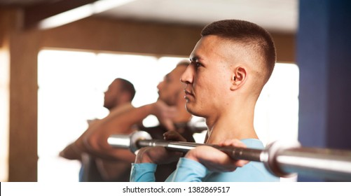 Young People in Gym Training With Barbells. Small Group of Male Athletes During Workout. Cross Fit Training. Sports, Fitness, Healthy Lifestyle and Teamwork