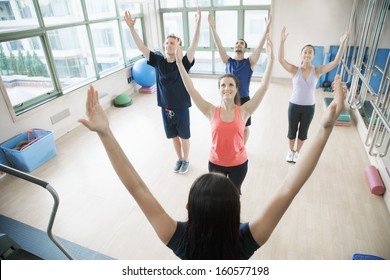 Young people with hands in air in yoga class