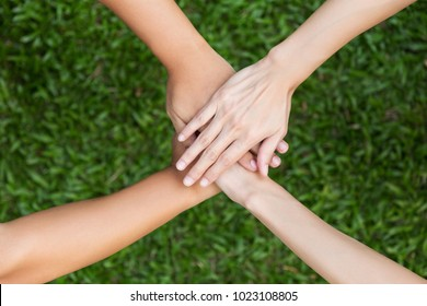 young people hands putting together on grass background, teamwork cooperation concept