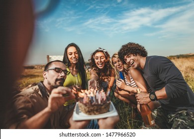 Young people have a good time in camp in nature. They're celebrating a birthday, laughing and greeting to their friend with birthday cake, happy to be together.