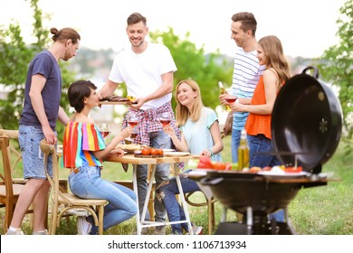 Young people having barbecue with modern grill outdoors