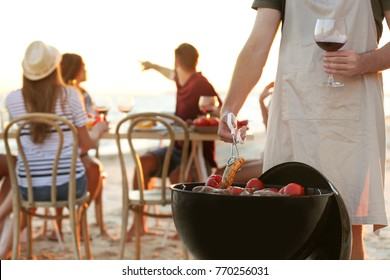 Young people having barbecue party on beach