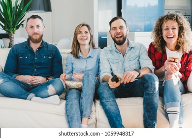 young people having day-off relaxing in front of tv in cozy living room. Four friends spending their weekend together sitting on sofa, eating popcorn and laughing over extremely amusing tv-show.