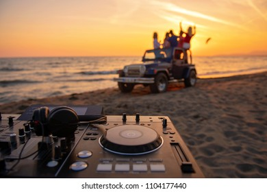 young people having fun in convertible car at the beach at sunset.