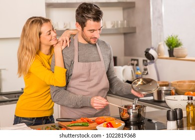 young people having fun cooking together in home kitchen